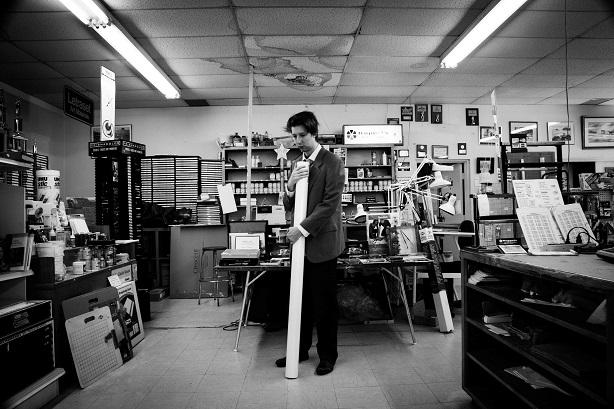 Emmanuel Schwartz tenant un rouleau de papier dont se servait Alfred McMoore pour faire ses tableaux, dans le magasin même où il s'approvisionnait. Ces grands rouleaux de papier font 42 pouces (107 centimètres) de hauteur.