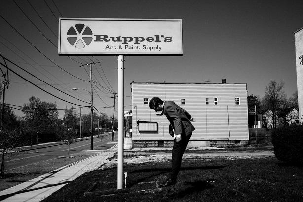 Emmanuel Schwartz devant l'enseigne de la boutique où Alfred achetait les grands rouleaux de papier servant à ses oeuvres